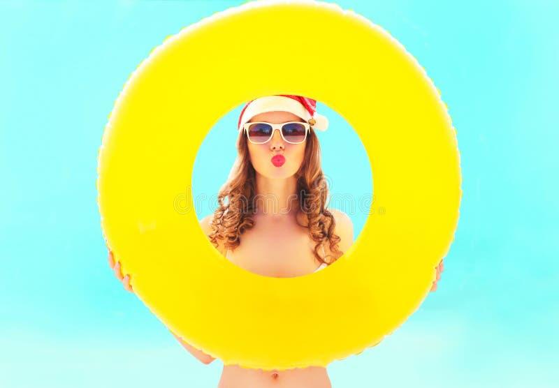 红色圣诞老人帽子的圣诞节画象俏丽的妇女有在海的圈子可膨胀的制造的空气亲吻的 免版税库存图片