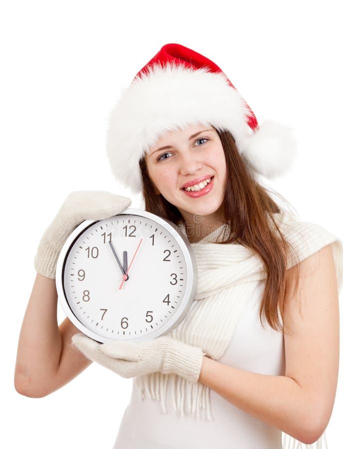 红色圣诞老人帽子的女孩与在白色的时钟 免版税图库摄影