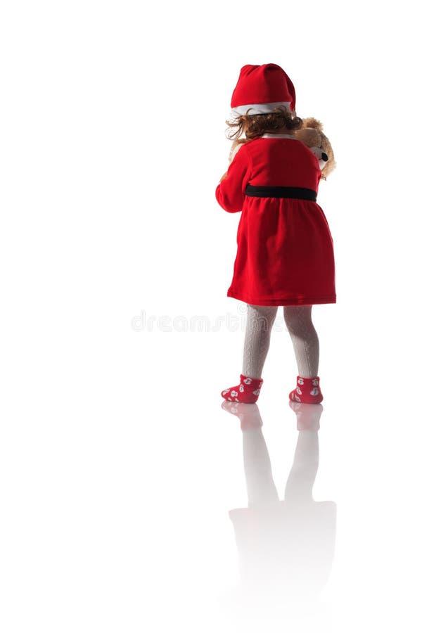 红色圣诞老人帽子的小女孩拿着在白色背景的玩具熊玩具 免版税库存照片