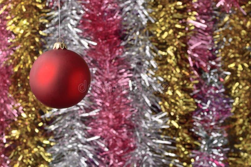 红色圣诞舞会 在模糊的彩色金属箔背景下 免版税库存照片