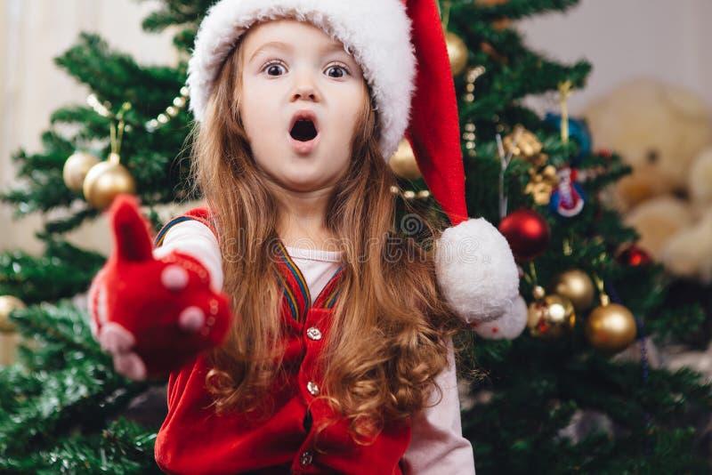 红色圣诞节帽子的惊奇的快乐的女孩 免版税图库摄影