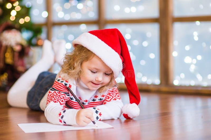 红色圣诞节帽子的愉快的女孩给圣诞老人写信 库存照片