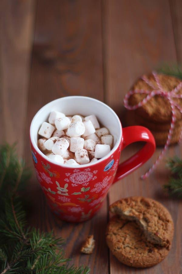红色圣诞节杯子咖啡和蛋白软糖和曲奇饼在木桌上 库存图片