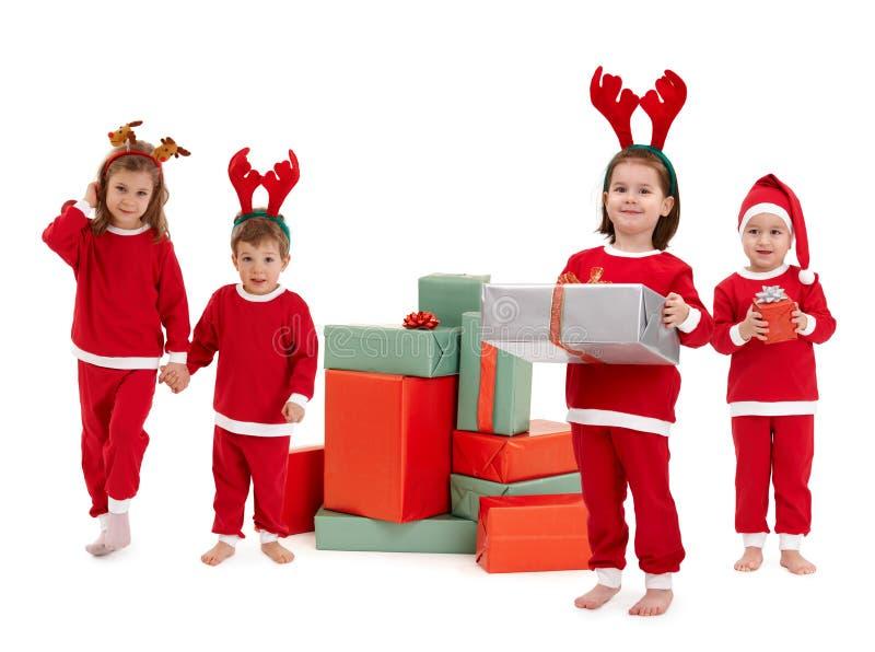红色圣诞节的小孩子穿戴与礼物 免版税图库摄影