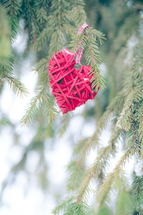 红色圣诞节装饰品,心脏,在圣诞树圣诞快乐贺卡 寒假题材 免版税库存照片
