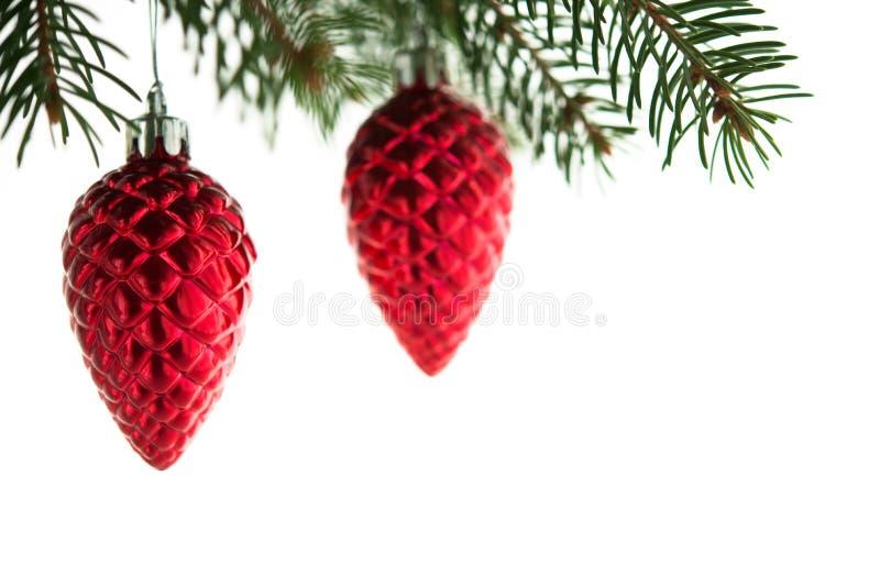 红色圣诞节装饰在xmas树的锥体在被隔绝的白色背景 免版税库存照片