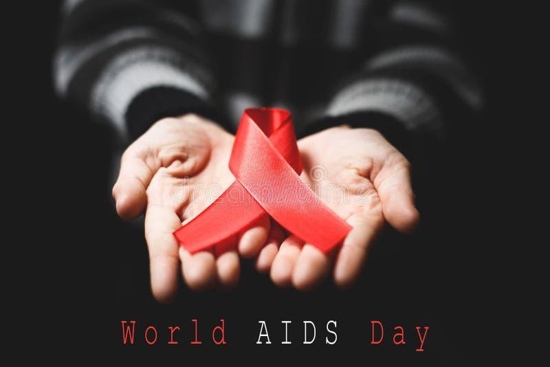 红色在手上援助丝带在黑背景和文本世界 免版税库存图片