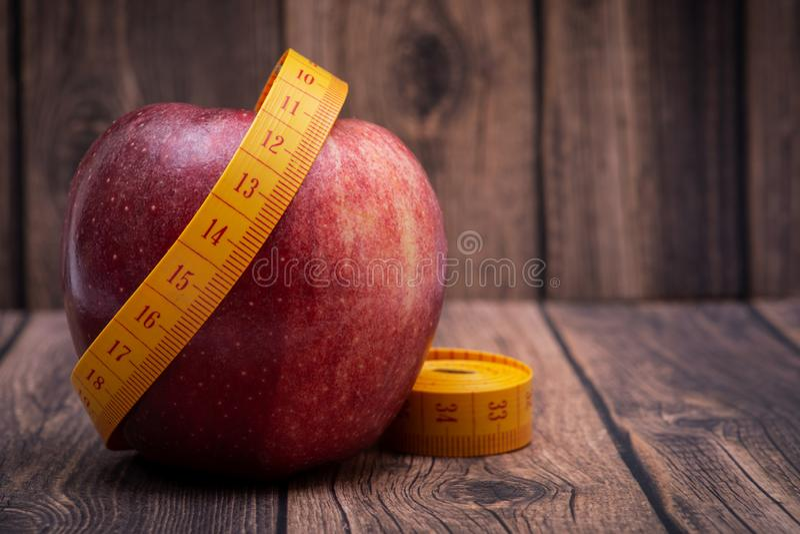 红色在木背景的苹果计算机和软的乙烯基测量的磁带 免版税库存照片