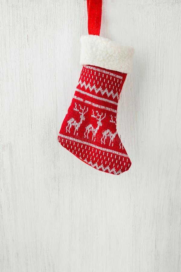 红色垂悬在白色木谷仓板火地方的被编织的圣诞节长袜 斯堪的纳维亚装饰品 欢乐明亮的舒适大气 库存照片