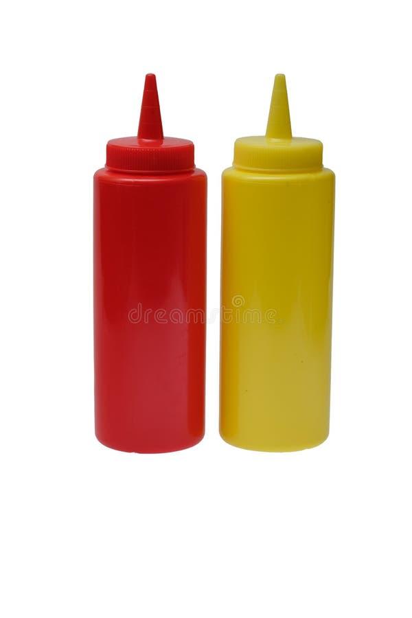 红色塑料番茄酱和黄色芥末塑料瓶在白色背景 免版税库存照片