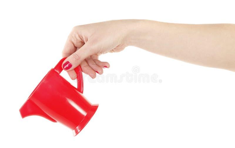 红色塑料水壶投手在手中 免版税图库摄影