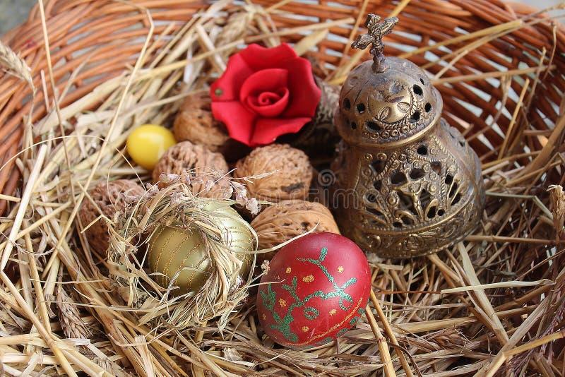 红色复活节彩蛋、核桃和教堂钟在一个被编织的篮子 库存照片