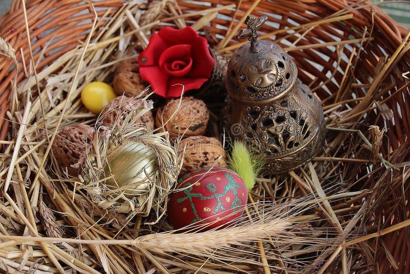 红色复活节彩蛋、核桃和教堂钟在一个被编织的篮子 图库摄影