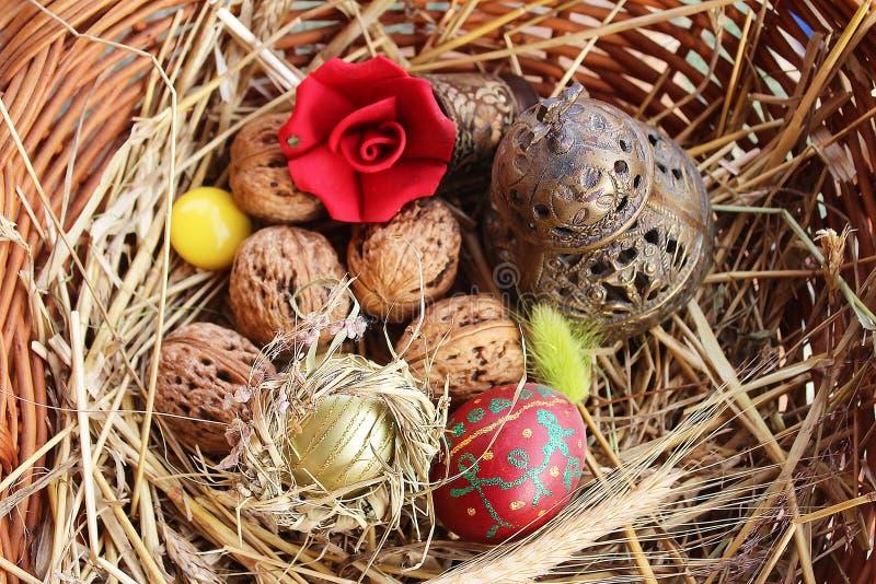 红色复活节彩蛋、核桃和教堂钟在一个被编织的篮子 库存图片