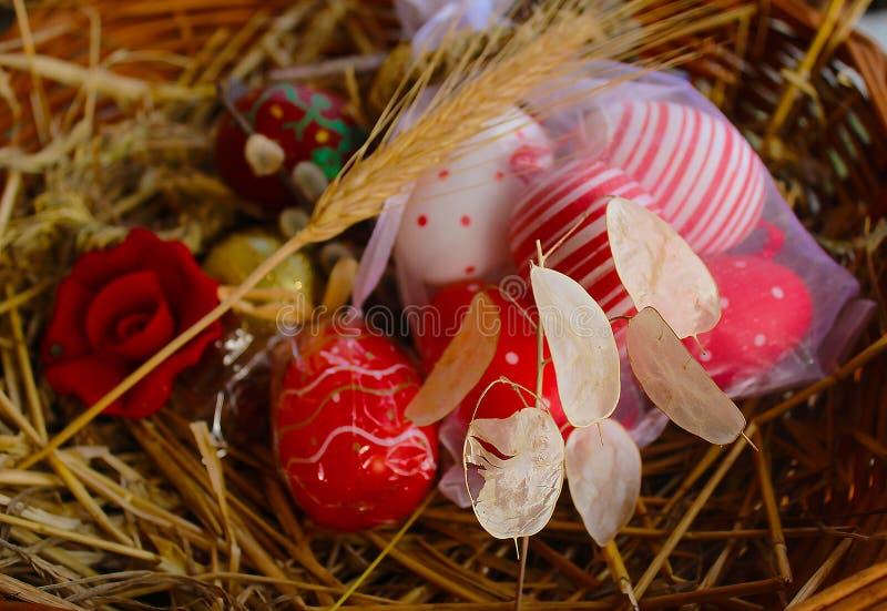 红色复活节彩蛋、核桃和教堂钟在一个被编织的篮子 免版税库存图片