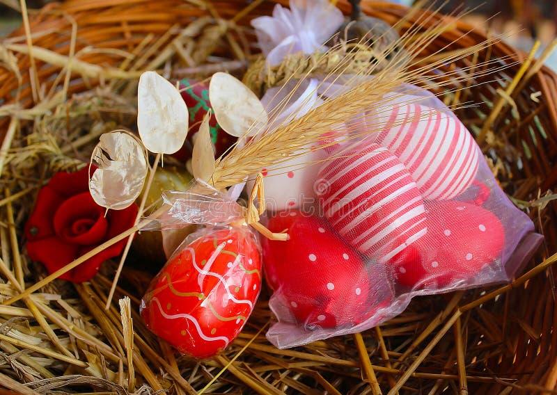 红色复活节彩蛋、核桃和教堂钟在一个被编织的篮子 免版税图库摄影