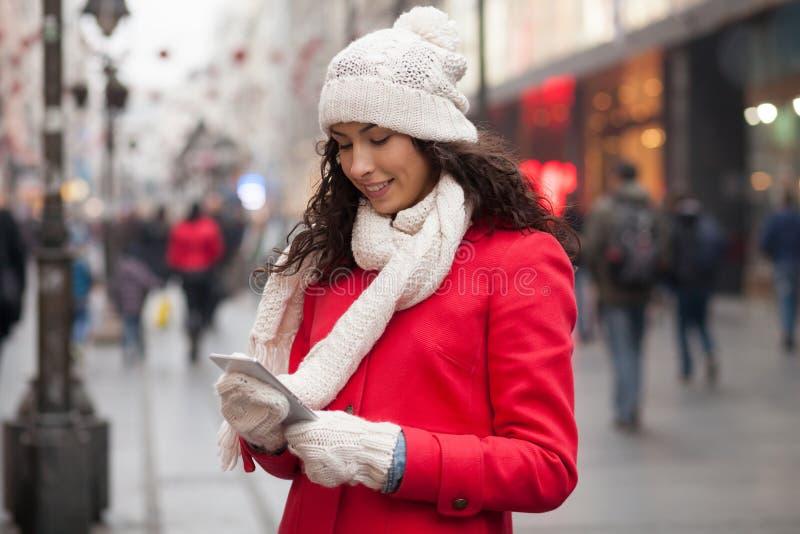 红色外套和羊毛盖帽的与智能手机的妇女和手套在韩 免版税图库摄影