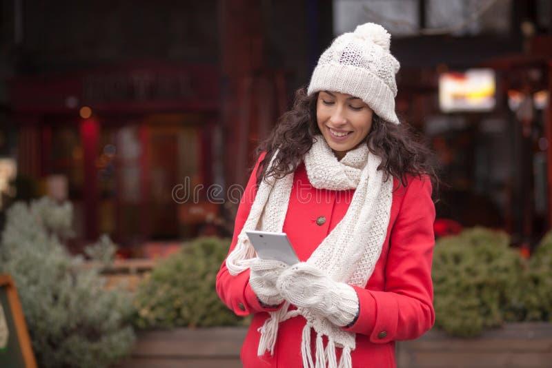 红色外套和羊毛盖帽的美丽的与smartph的妇女和手套 免版税库存照片