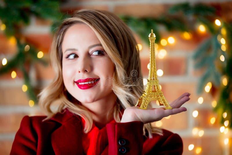 红色外套的女孩有金黄埃佛尔铁塔纪念品的 免版税库存图片