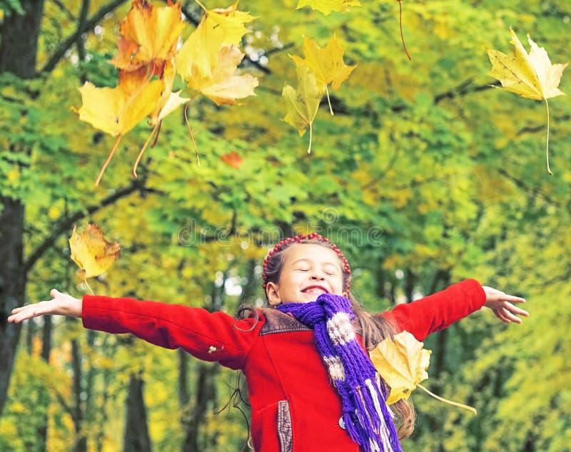 红色外套的小笑的俏丽的女孩在秋天公园投掷黄色叶子 免版税库存图片