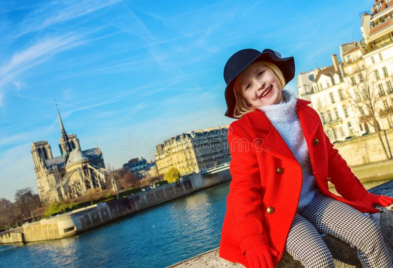 红色外套的愉快的现代女孩在堤防在巴黎,法国 库存照片