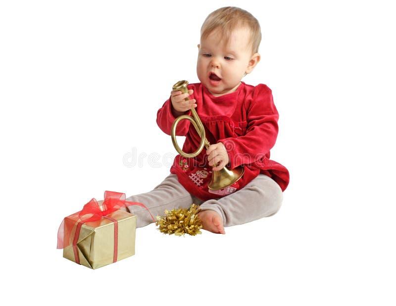 红色天鹅绒礼服的婴孩检查玩具垫铁 免版税库存照片