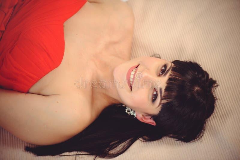 红色天 一件红色礼服的爱的女孩A女孩在一张明亮的床上说谎 从轻的织品的背景 在a中流传的红色口红 库存照片