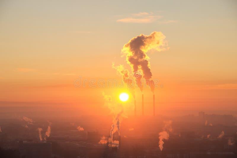 红色太阳在工业重镇的天际升起  来自热电厂管子的烟 日出空中射击  免版税图库摄影