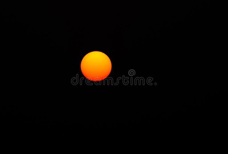 红色太阳在黑背景中 免版税库存图片