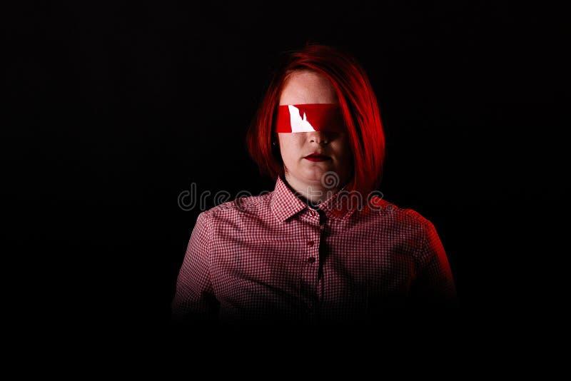 红色头发女孩在有红色衣裳、接近的画象、妇女T恤杉的和牛仔裤的黑暗的演播室 与透明胶带的面孔在眼睛 C 库存图片