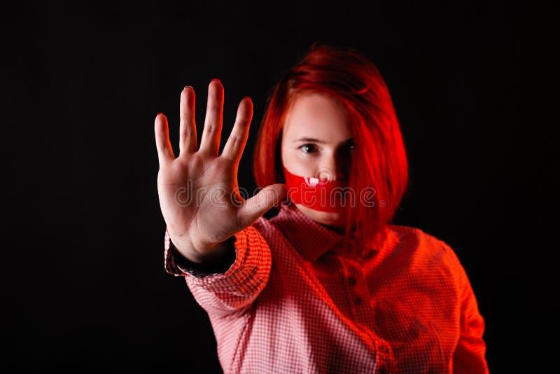 红色头发女孩在有红色衣裳、接近的画象、妇女T恤杉的和牛仔裤的黑暗的演播室 与透明胶带的面孔在嘴 库存照片
