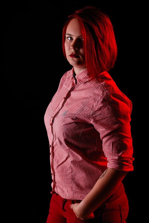 红色头发女孩在有红色衣裳、接近的画象、妇女T恤杉的和牛仔裤的黑暗的演播室 免版税库存照片