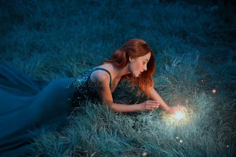 红色头发年轻女人在一件美妙的礼服的草说谎有长的火车的 库存图片