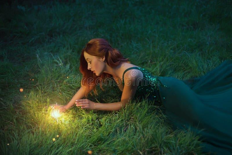 红色头发迷人的妇女在一件美妙的鲜绿色礼服的草说谎有长的火车的 免版税库存照片