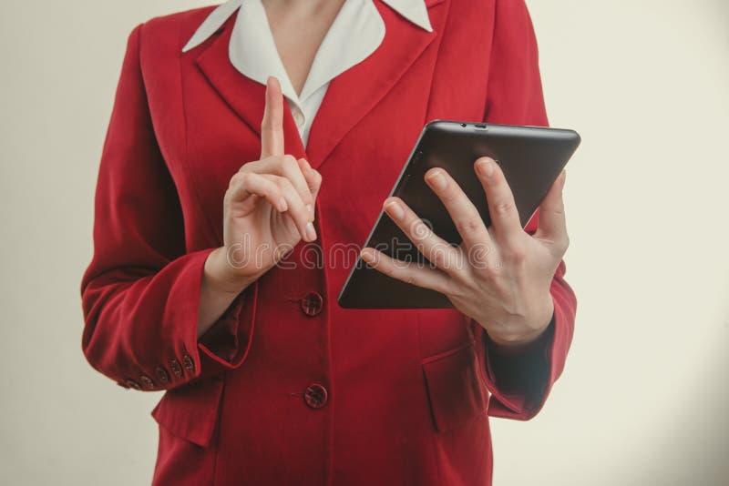 红色夹克手指的企业女孩在片剂 库存照片