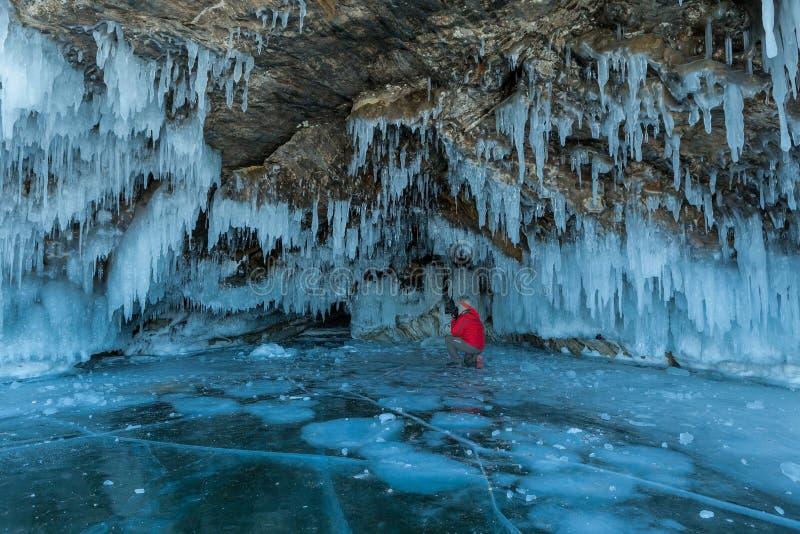 红色夹克的一个游人拍冰柱洞,贝加尔湖照片  免版税库存图片