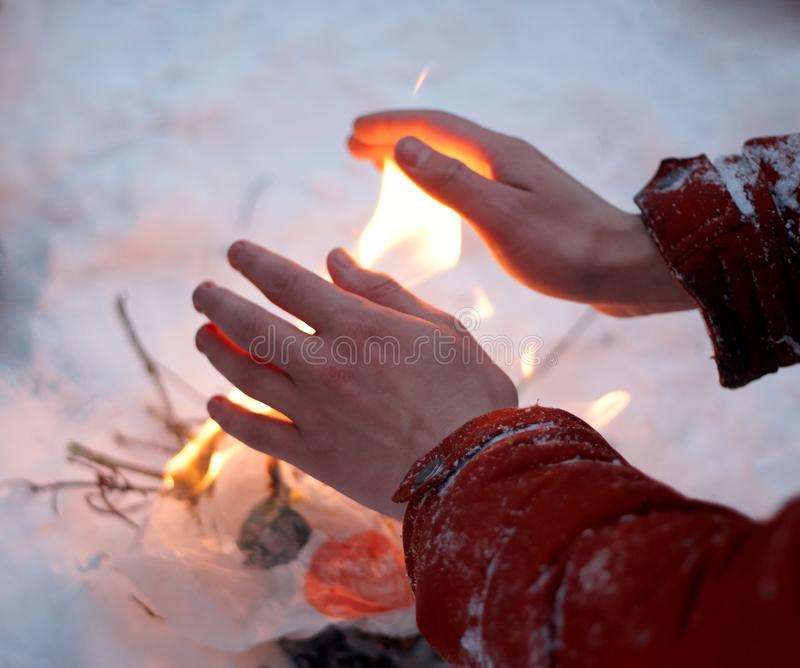 红色夹克的人温暖冻结的手 图库摄影