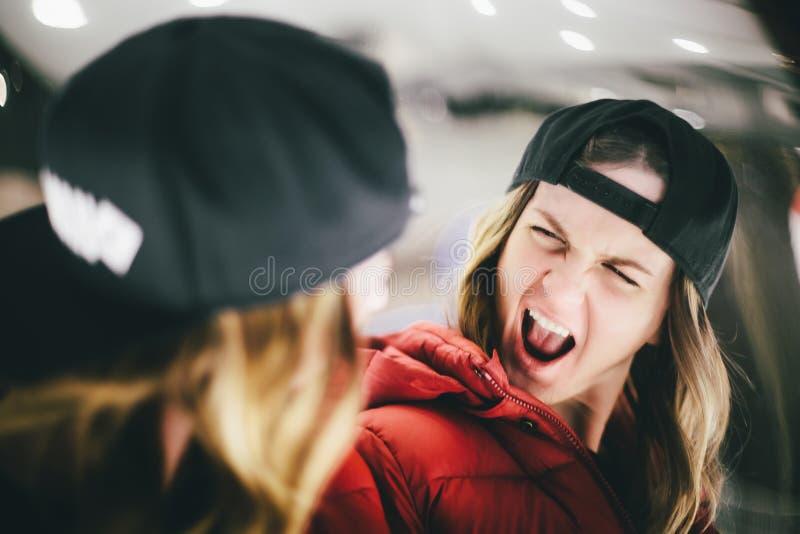 红色夹克的女孩戴着时髦的帽子做鬼脸在错误玻璃的 免版税库存图片