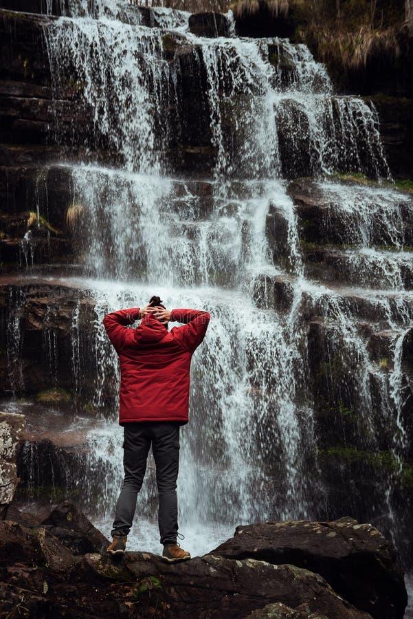 红色夹克的女孩由瀑布 图库摄影