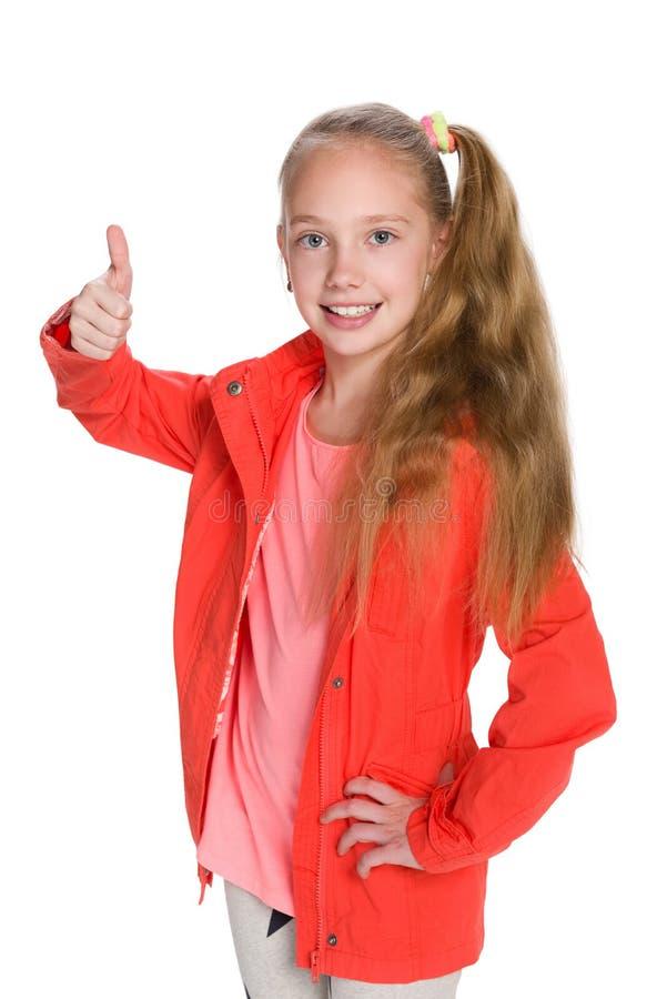 红色夹克的小女孩举行她的赞许 库存图片