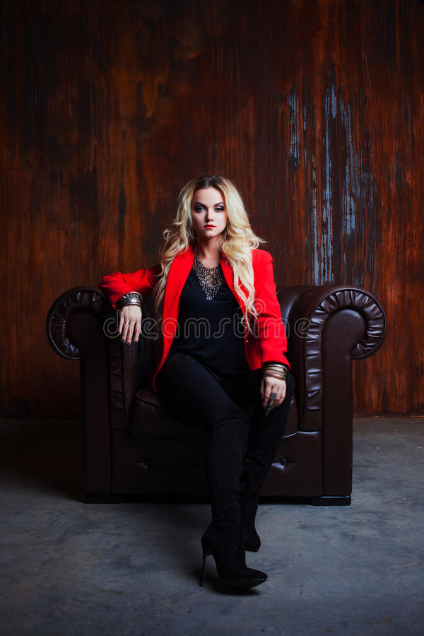 红色夹克的年轻和可爱的白肤金发的妇女在皮革扶手椅子,背景难看的东西生锈的墙壁坐 免版税库存照片