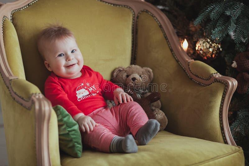 红色套头衫微笑的小逗人喜爱的男孩,当坐在古板的扶手椅子在圣诞树附近在屋子里时 关闭射击 图库摄影