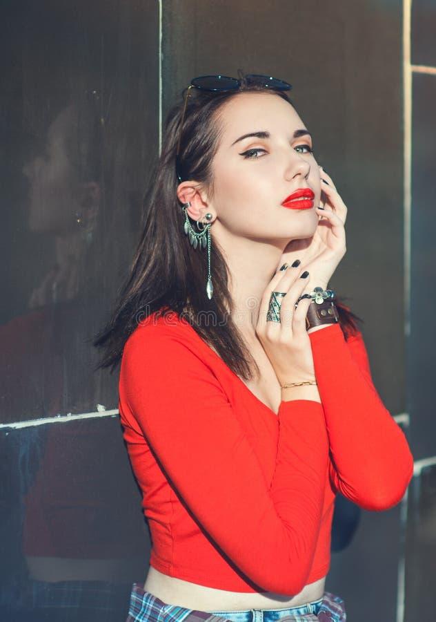 红色女衬衫的年轻美丽的行家女孩有太阳镜的 免版税库存照片