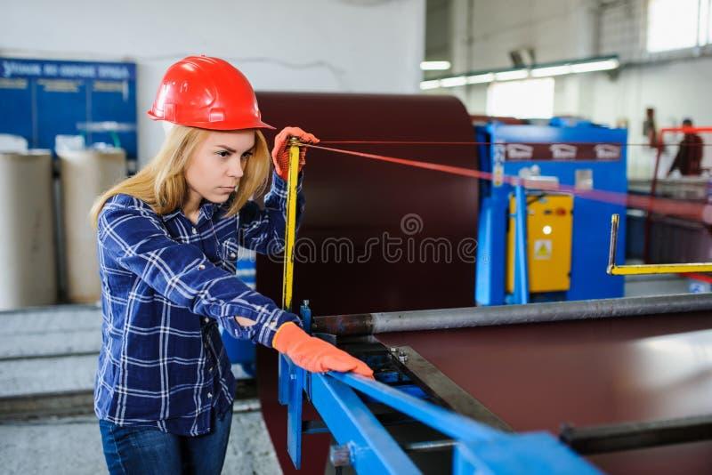 红色安全帽的妇女在金属瓦屋顶制造业事实 免版税库存照片