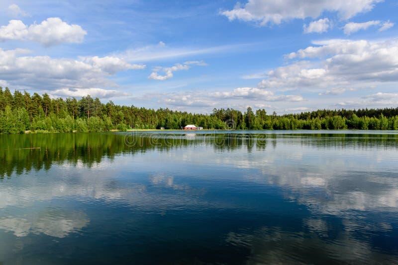 红色小屋在蓝色湖的岸的森林里 免版税库存照片