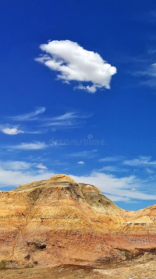 红色小山蓝天白色云彩 库存图片