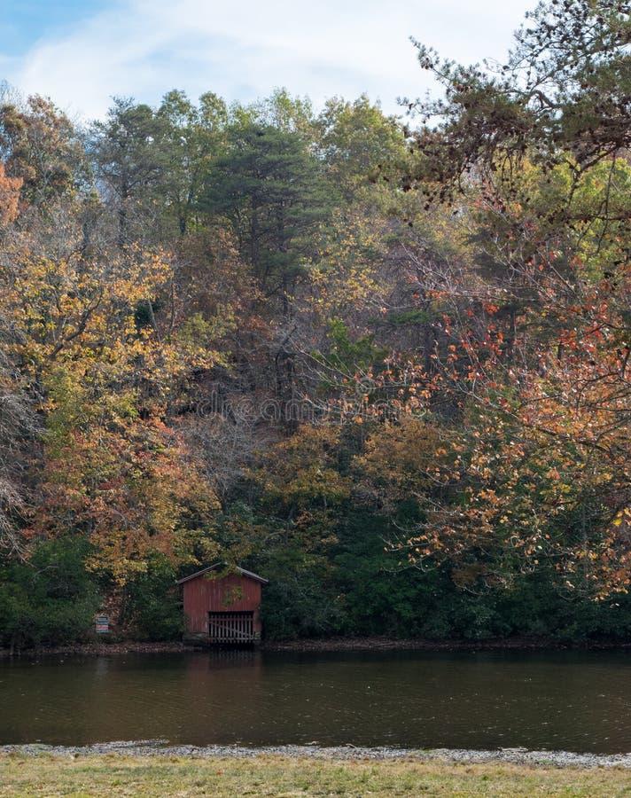 红色小船船坞在水` s边缘流洒了在森林里 免版税库存图片