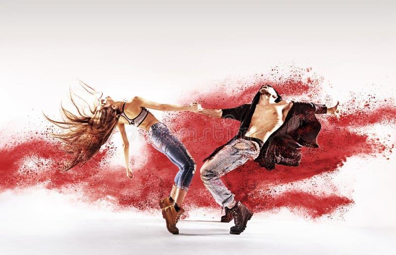 洒红色尘土的有天才的年轻舞蹈家 免版税库存照片