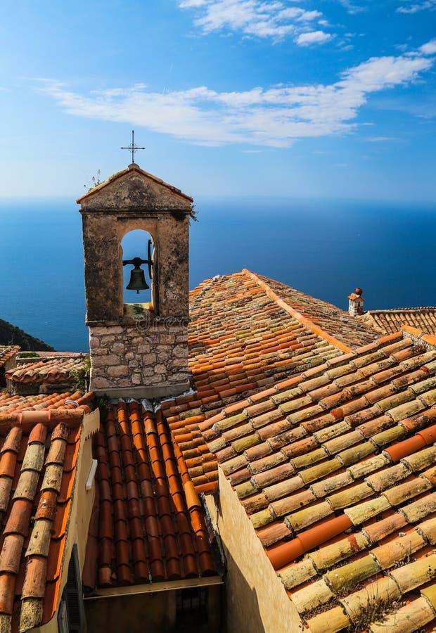红色屋顶教堂十字架有在法国人的地中海视图 免版税库存图片