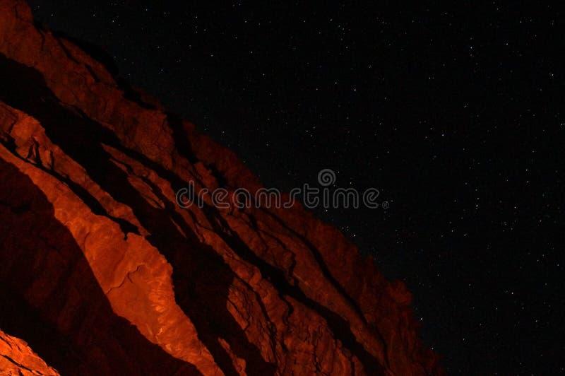红色山在沙漠在与明亮的星的晚上 免版税库存照片